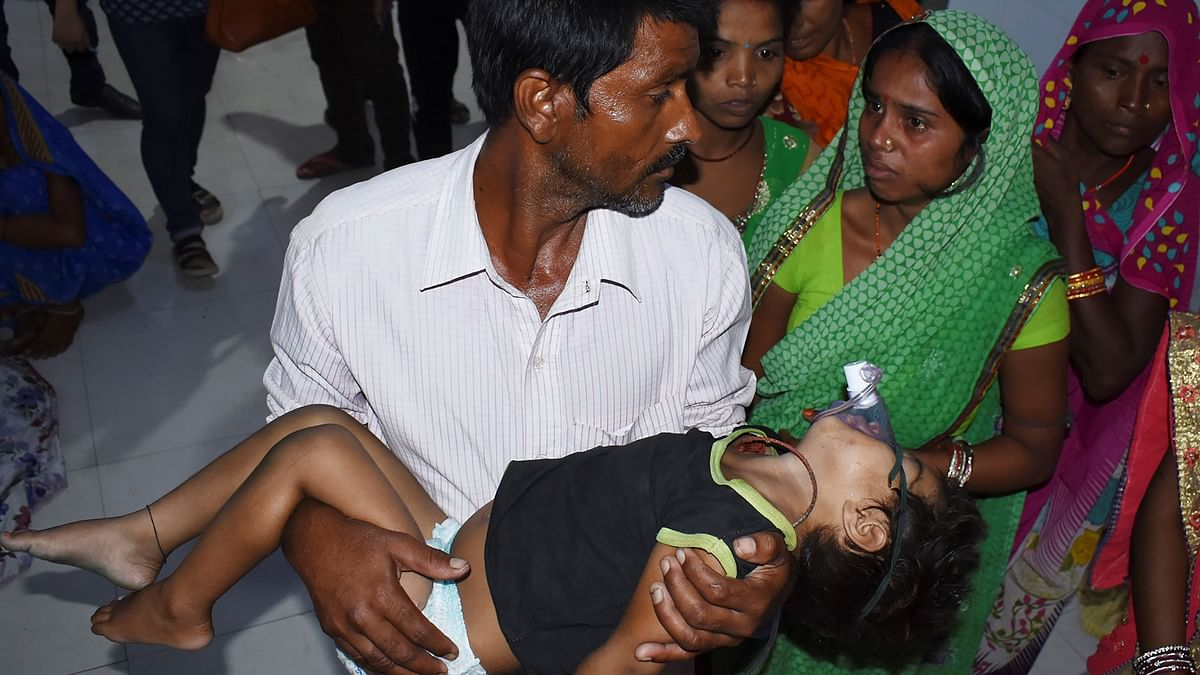 Father (C) of four-year-old Khushbu Kumari carries his son, who is suffering from Acute Encephalitis Syndrome (AES), at Kejriwal hospital along with relatives before going to another hospital in Muzaffarpur in Bihar.