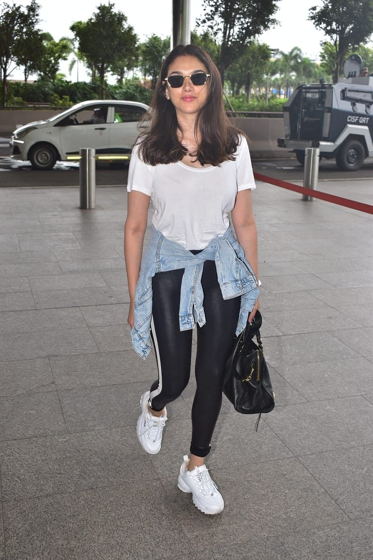 Aditi on the other hand was spotted in a casual airport look with a simple white tee, black leggings and a denim jacket wrapped around her waist. She paired the look with black bag and white sneakers.