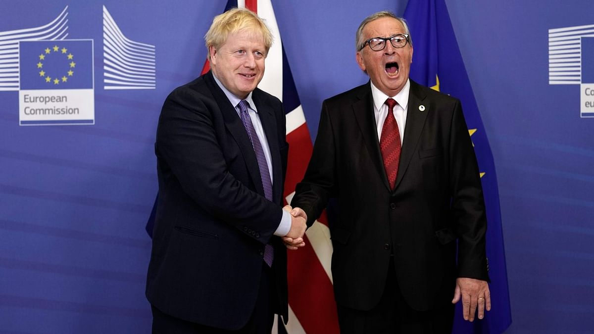 British Prime Minister Boris Johnson (L) shakes hands with President of the European Commission Jean-Claude Juncker as they prepare to address a press conference at a European Union Summit at European Union Headquarters in Brussels on October 17, 2019.