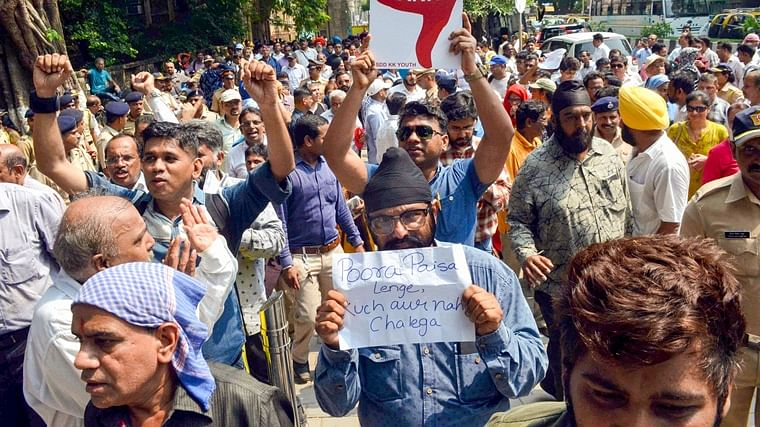 PMC Bank customers stage a protest outside the Killa Court, where the accused of the bank scam were being produced, in Mumbai, Monday.