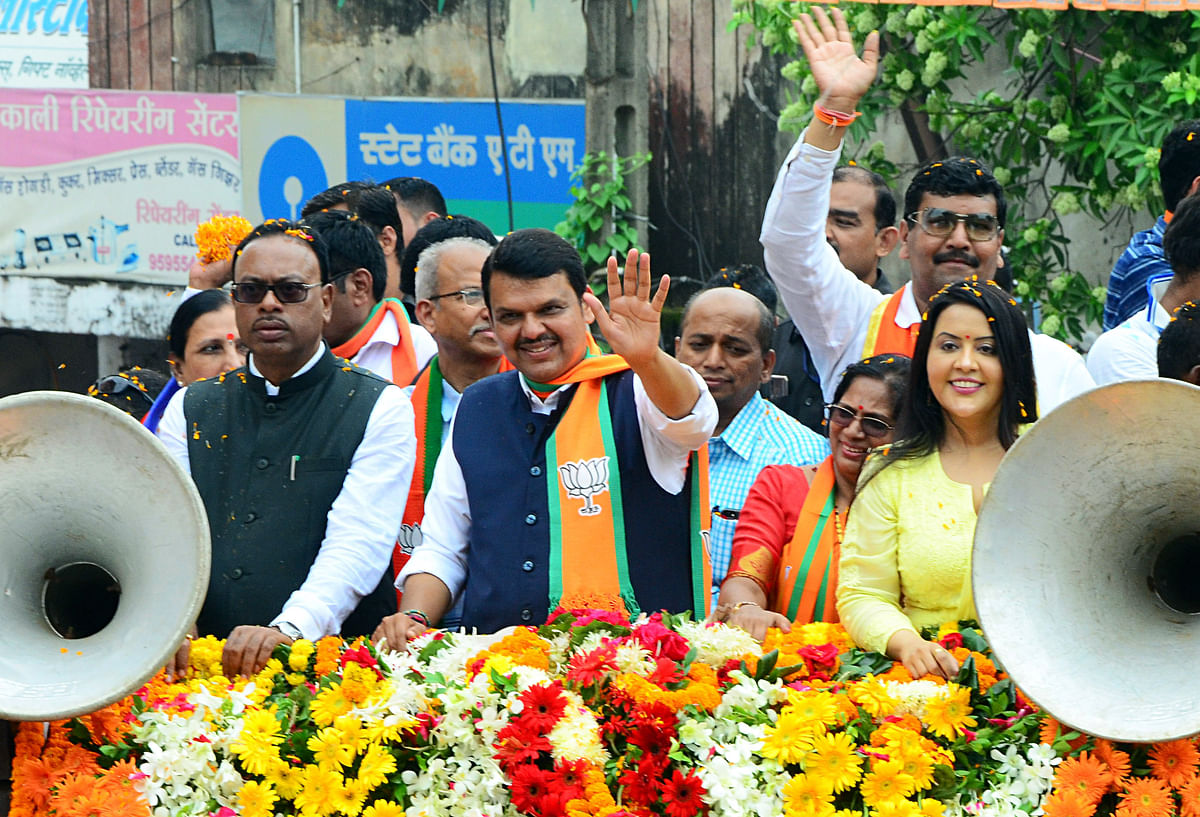 Maharashtra Chief Minister Devendra Fadnavis waves to his supporters during a mega roadshow ahead of the Assembly polls, in Nagpur on Saturday