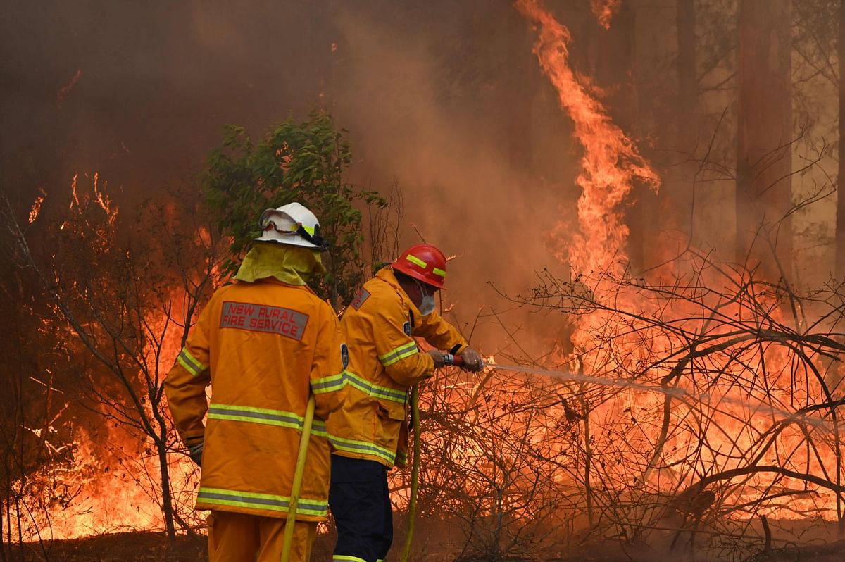 Firefighters tackle a bushfire to save a home in Taree, 350km north of Sydney on November 9, 2019.