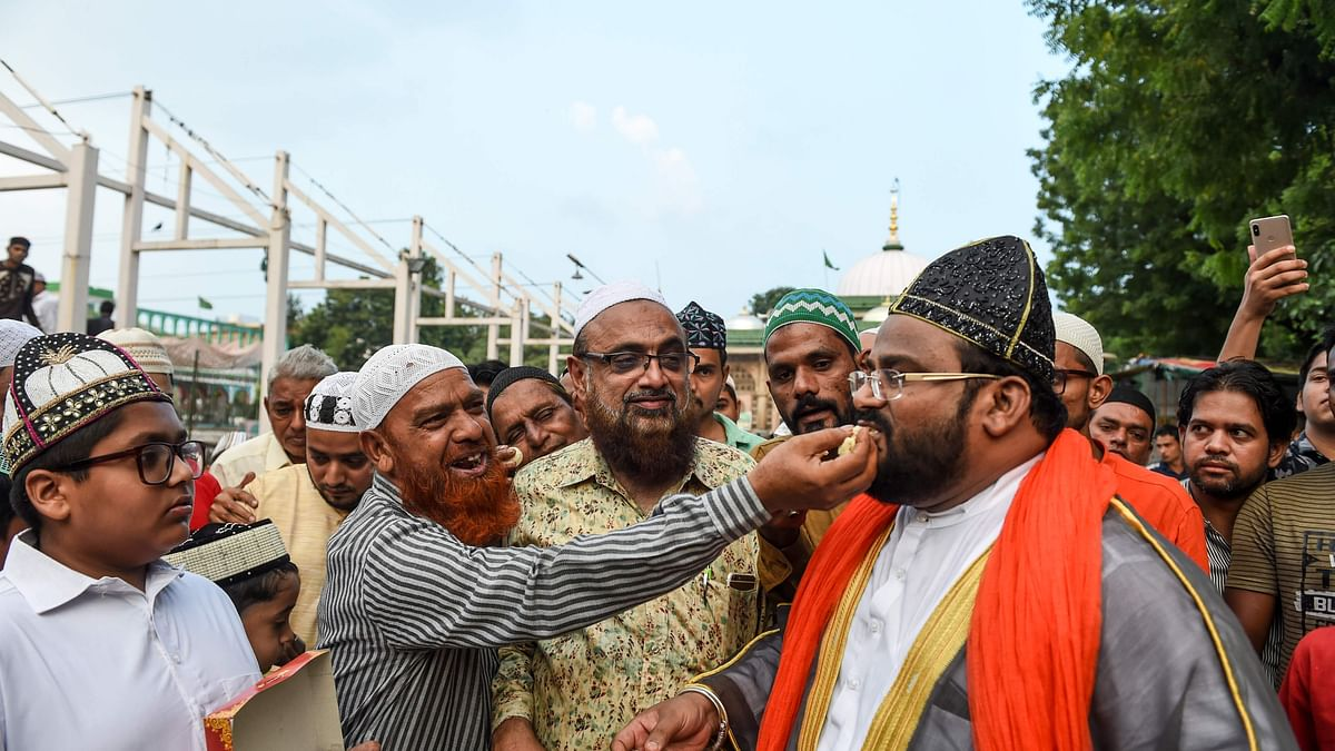 Muslims offer sweets to each other after Supreme Court's verdict outside the Shah-e-alam shrine in Ahmedabad, India, Saturday, Nov. 9,  2019.