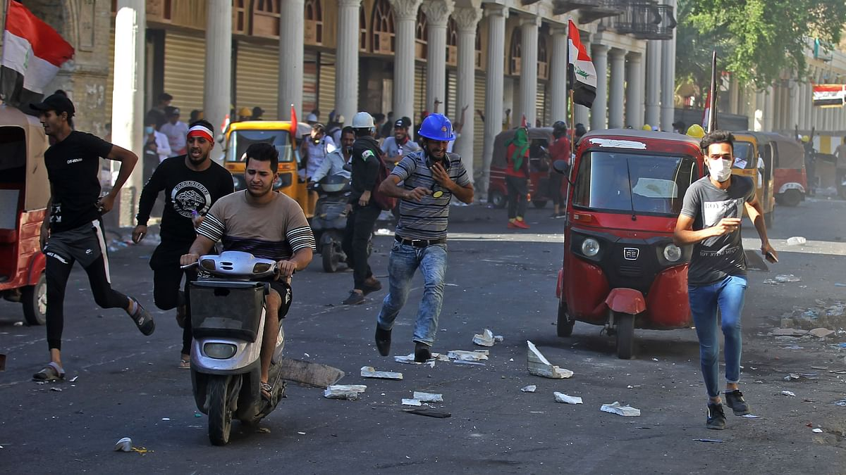 Iraqi protesters run asthey clash with security forces in the capital Baghdad during ongoing anti-government demonstrations on November 8, 2019.