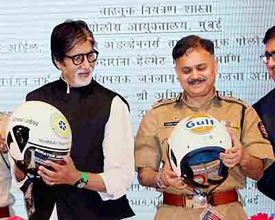 Mumbai: Mumbai Police Commissioner Javed Ahmed and Bollywood megastar Amitabh Bachchan during the helmet distribution to traffic policemen in Mumbai on Monday. PTI Photo (PTI9_15_2015_000032B)