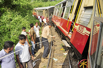 People gather at the site of the derailment of a chartered narrow gauge train at Parwanoo on the Kalka-Shimla Unesco Heritage Track on September 12, 2015.  Two British tourists were killed and nine other passengers injured when a train carrying tourists to the hill town of Shimla in northern India derailed, police said.       AFP PHOTO/ BHAWNA SETHI