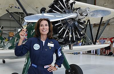 Adventurer Tracey Curtis-Taylor holds up a glass of champagne next to her vintage, open-cockpit 1942 Boeing Stearman aircraft after landing at Sydney International airport in Sydney on January 9, 2016. Curtis-Taylor completed an epic, three-month solo flight from Britain to Australia flying 13,000 miles (nearly 21,000 kilometres) spanning 23 countries and was modeled after British aviatrix Amy Johnson's flight from Britain to Australia in 1930 in what is known as one of the greatest solo flight achievements in history.   AFP PHOTO / Peter PARKS