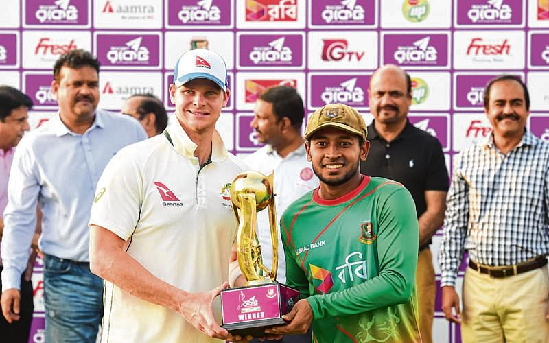 Australian cricket captain Steven Smith (L) and Bangladeshi cricket captain Mushfiqur Rahim (R) hold the tournament trophy during the presentation ceremony following the second cricket Test between Bangladesh and Australia at Zahur Ahmed Chowdhury Stadium in Chittagong on September 7, 2017. / AFP PHOTO / Munir UZ ZAMAN