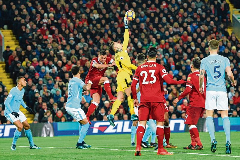 Manchester City's Brazilian goalkeeper Ederson (C) comes out to punch the ball during the English Premier League football match between Liverpool and Manchester City at Anfield in 2018.