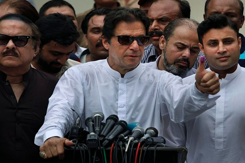 Islamabad: Pakistani politician Imran Khan, chief of Pakistan Tehreek-e-Insaf party, shows his marked thumb after casting his vote at a polling station for the parliamentary elections in Islamabad, Pakistan, Wednesday, July 25, 2018. After an acrimonious campaign, polls opened in Pakistan on Wednesday to elect the country's third straight civilian government, a first for this majority Muslim nation that has been directly or indirectly ruled by its military for most of its 71-year history. AP/PTI(AP7_25_2018_000055B)