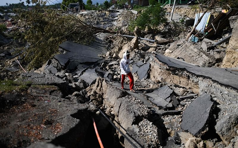 A survivor walks along a destroyed road in Palu, Indonesia's Central Sulawesi. Photo by Jewel SAMAD / AFP